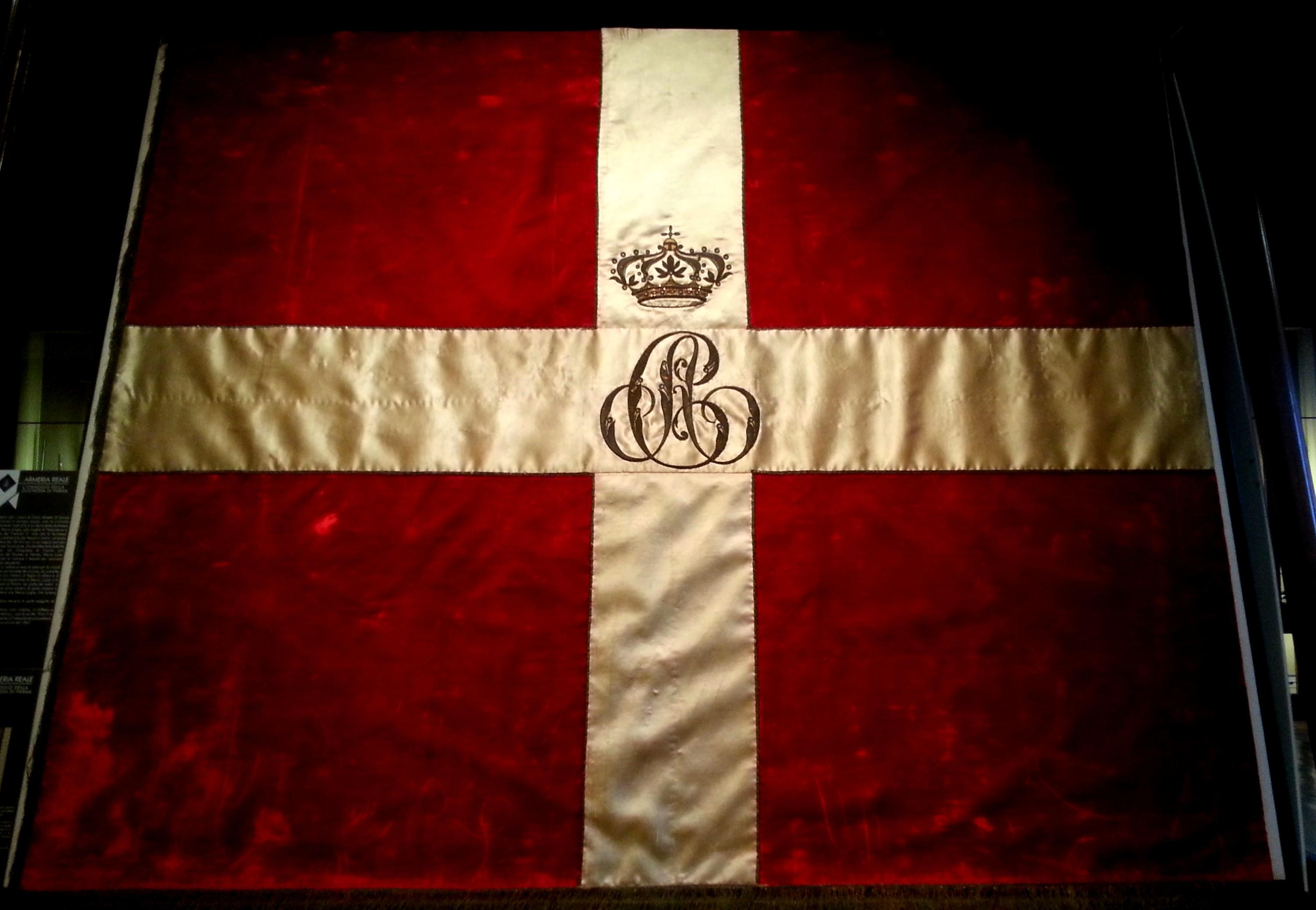 Bandiera degli Stati di Savoia con monogramma centrale di re Carlo Alberto (conservata presso l'Armeria Reale di Torino)